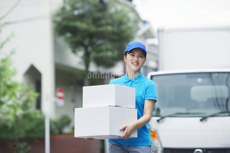 作業服を着て笑顔で荷物を運ぶ若い女性の写真素材 [FYI04595982]
