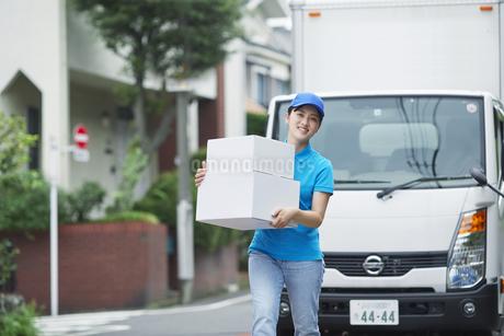 作業服を着て笑顔で荷物を運ぶ若い女性の写真素材 [FYI04595983]