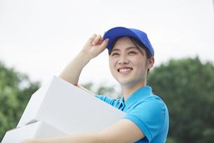 作業服を着て笑顔で荷物を運ぶ若い女性の写真素材 [FYI04595984]