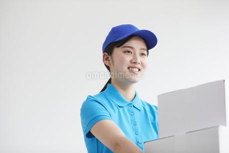 作業服を着て笑顔で荷物を運ぶ若い女性の写真素材 [FYI04595985]