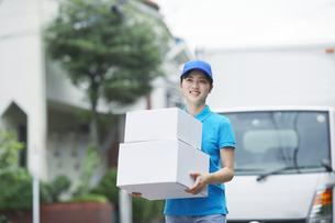 作業服を着て笑顔で荷物を運ぶ若い女性の写真素材 [FYI04595986]