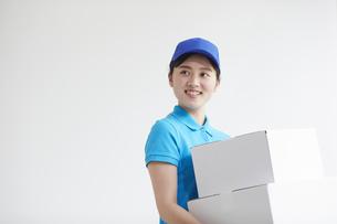 作業服を着て笑顔で荷物を運ぶ若い女性の写真素材 [FYI04595987]