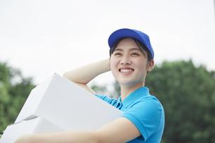 作業服を着て笑顔で荷物を運ぶ若い女性の写真素材 [FYI04595988]
