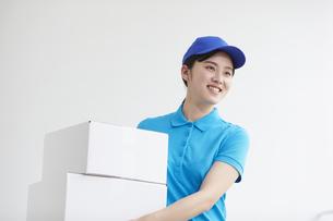 作業服を着て笑顔で荷物を運ぶ若い女性の写真素材 [FYI04595989]