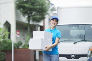 作業服を着て笑顔で荷物を運ぶ若い女性の写真素材 [FYI04595990]