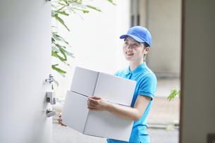 作業服を着て笑顔で荷物を運ぶ若い女性の写真素材 [FYI04595991]