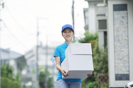 作業服を着て笑顔で荷物を運ぶ若い女性の写真素材 [FYI04595992]