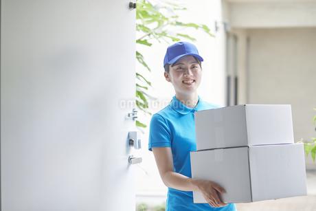 作業服を着て笑顔で荷物を運ぶ若い女性の写真素材 [FYI04595993]