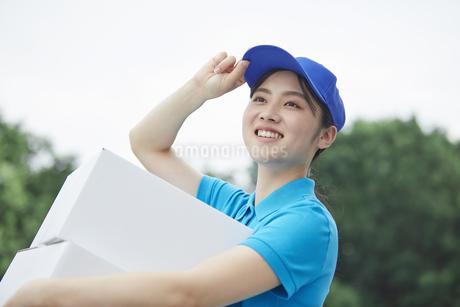 作業服を着て笑顔で荷物を運ぶ若い女性の写真素材 [FYI04595994]