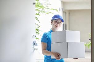 作業服を着て笑顔で荷物を運ぶ若い女性の写真素材 [FYI04595995]