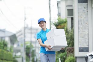 作業服を着て笑顔で荷物を運ぶ若い女性の写真素材 [FYI04595996]