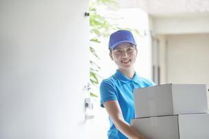 作業服を着て笑顔で荷物を運ぶ若い女性の写真素材 [FYI04595997]