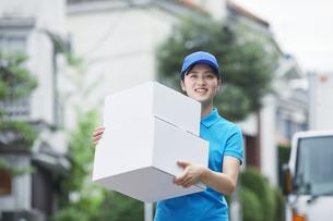 作業服を着て笑顔で荷物を運ぶ若い女性の写真素材 [FYI04595999]