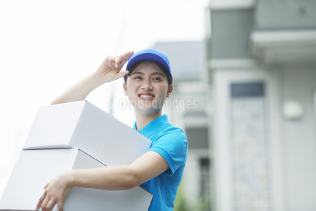 作業服を着て笑顔で荷物を運ぶ若い女性の写真素材 [FYI04596000]