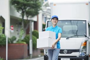 作業服を着て笑顔で荷物を運ぶ若い女性の写真素材 [FYI04596001]