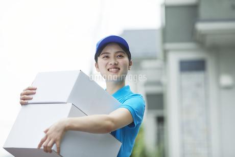 作業服を着て笑顔で荷物を運ぶ若い女性の写真素材 [FYI04596002]