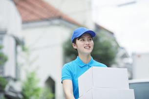 作業服を着て笑顔で荷物を運ぶ若い女性の写真素材 [FYI04596003]