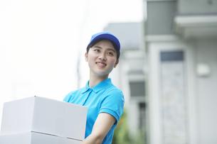 作業服を着て笑顔で荷物を運ぶ若い女性の写真素材 [FYI04596004]
