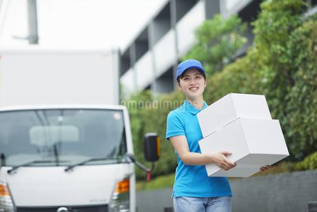 作業服を着て笑顔で荷物を運ぶ若い女性の写真素材 [FYI04596005]