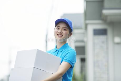 作業服を着て笑顔で荷物を運ぶ若い女性の写真素材 [FYI04596006]