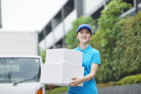 作業服を着て笑顔で荷物を運ぶ若い女性の写真素材 [FYI04596007]
