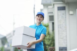 作業服を着て笑顔で荷物を運ぶ若い女性の写真素材 [FYI04596008]
