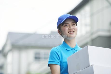 作業服を着て笑顔で荷物を運ぶ若い女性の写真素材 [FYI04596009]