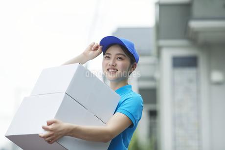作業服を着て笑顔で荷物を運ぶ若い女性の写真素材 [FYI04596010]