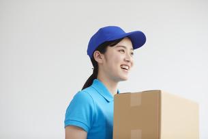 作業服を着て笑顔で荷物を運ぶ若い女性の写真素材 [FYI04596011]
