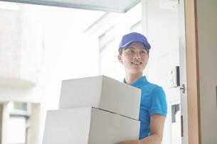 作業服を着て笑顔で荷物を運ぶ若い女性の写真素材 [FYI04596012]