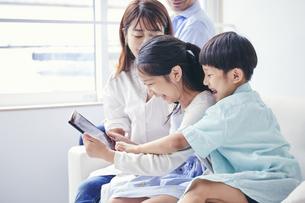 家の中でタブレットPCを観る笑顔の家族の写真素材 [FYI04596492]
