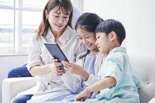 家の中でタブレットPCを観る笑顔の家族の写真素材 [FYI04596494]