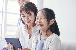 家の中でタブレットPCを観る笑顔の家族の写真素材 [FYI04596499]