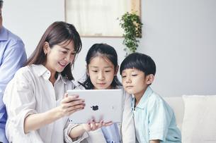 家の中でタブレットPCを観る笑顔の家族の写真素材 [FYI04596505]