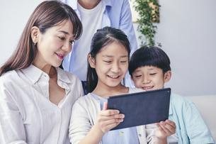家の中でタブレットPCを観る笑顔の家族の写真素材 [FYI04596516]