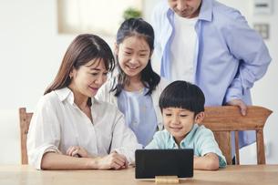家の中でタブレットPCを観る笑顔の家族の写真素材 [FYI04596520]