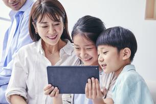 家の中でタブレットPCを観る笑顔の家族の写真素材 [FYI04596522]