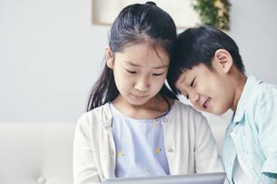 家の中でタブレットPCを観る笑顔の兄弟の写真素材 [FYI04596524]