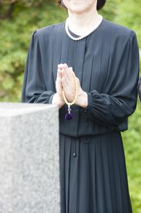 お墓に手を合わせる女性の写真素材 [FYI04598688]