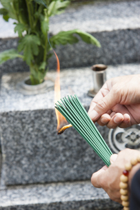 お線香に火をつける男性の写真素材 [FYI04598788]