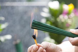 お線香に火をつける男性の写真素材 [FYI04598789]