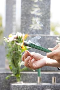 お線香に火をつける男性の写真素材 [FYI04598791]