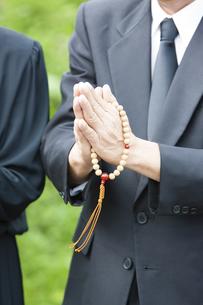 お墓に手を合わせる夫婦の写真素材 [FYI04598836]