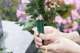 お線香を供える女性の写真素材 [FYI04598843]