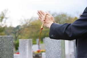 お墓に手を合わせる男性の写真素材 [FYI04598846]