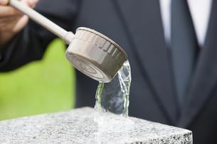 墓石に水をかける男性の写真素材 [FYI04598849]