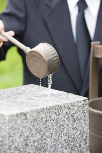 墓石に水をかける男性の写真素材 [FYI04598850]