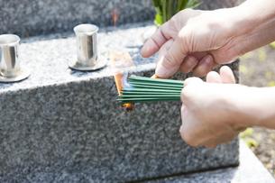 お線香に火をつける人の写真素材 [FYI04598857]
