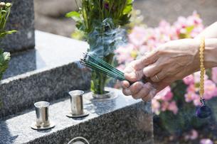 お線香を供える女性の写真素材 [FYI04598861]