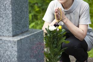 お墓に手を合わせる女性の写真素材 [FYI04598866]